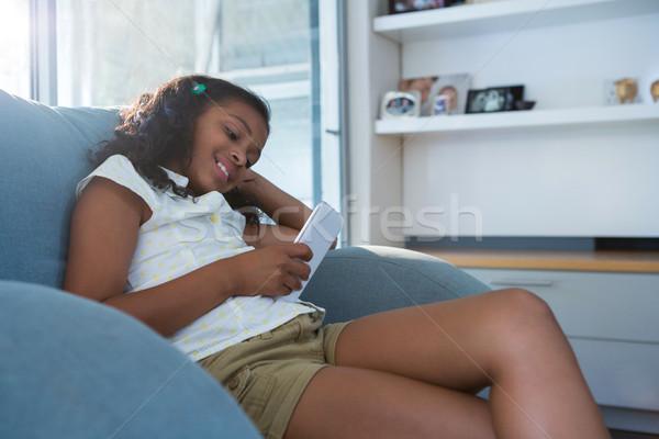 улыбаясь девушки таблетка сидят кресло гостиной Сток-фото © wavebreak_media