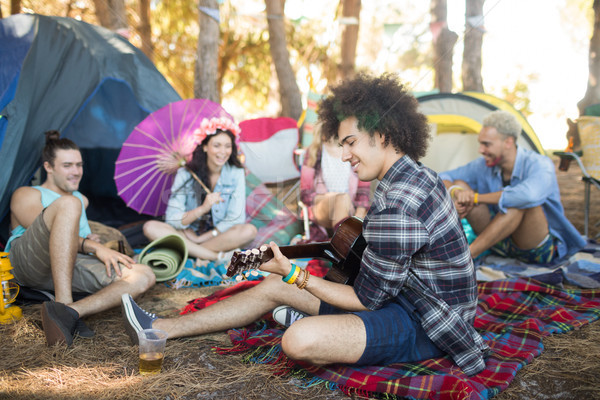 Stock photo: Young man playing guitar while sitting with friends at campsite