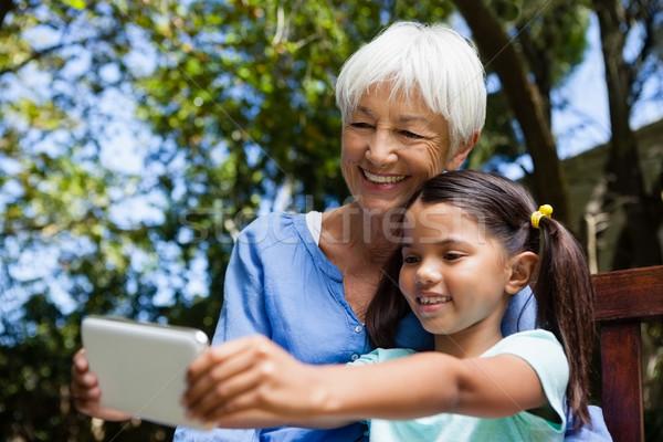 Mosolyog nagymama leányunoka elvesz ül pad Stock fotó © wavebreak_media