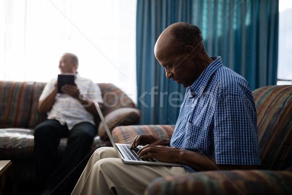Kıdemli adam dizüstü bilgisayar kullanıyorsanız oturma kanepe arkadaş Stok fotoğraf © wavebreak_media