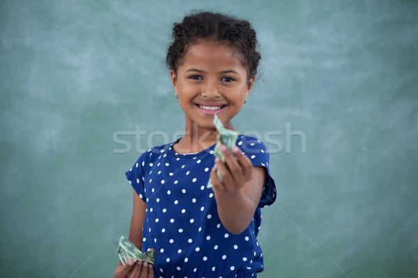 Portrait of girl giving paper currency Stock photo © wavebreak_media