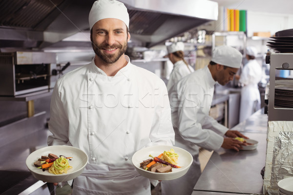 Smiling chef holding delicious dish in kitchen Stock photo © wavebreak_media