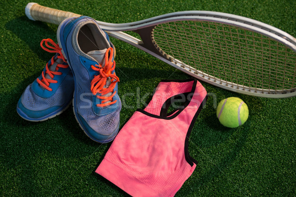 Sports shoes with tennis ball and racket by sports bra Stock photo © wavebreak_media