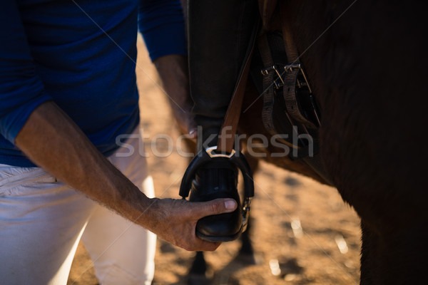 Midsection of male trainer adjusting woman leg on stirrup Stock photo © wavebreak_media