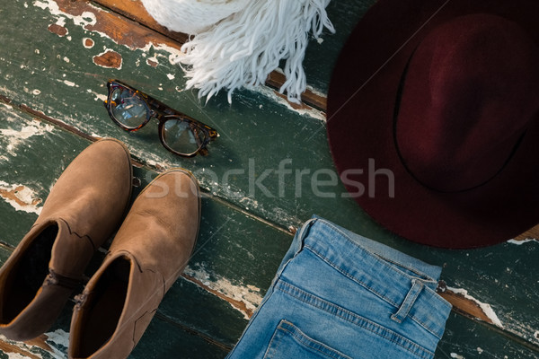 High angle view of shoe and jeans with personal accessories on wooden table Stock photo © wavebreak_media