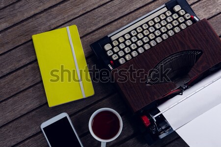 Overhead of vintage typewriter, diary, black coffee and smart phone on wooden table Stock photo © wavebreak_media