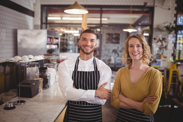 Portrait of smiling young wait staff standing with arms crossed by counter Stock photo © wavebreak_media