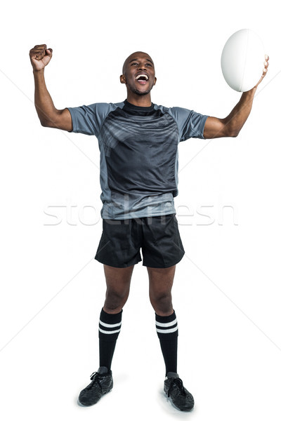 Cheerful sportsman with clenched fist holding rugby ball Stock photo © wavebreak_media
