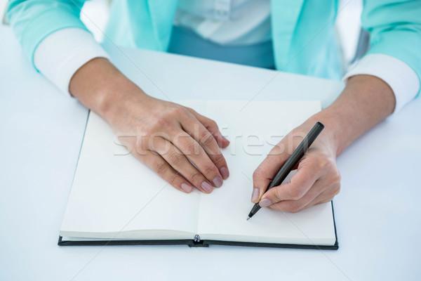 Businesswoman writing into her notepad Stock photo © wavebreak_media