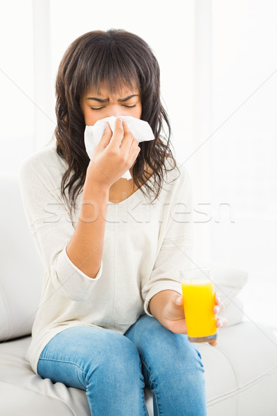 Pretty woman sneezing on couch Stock photo © wavebreak_media
