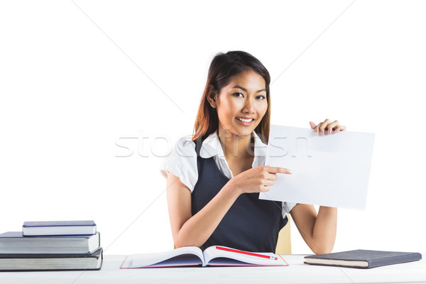 Smiling businesswoman pointing a sheet of paper Stock photo © wavebreak_media