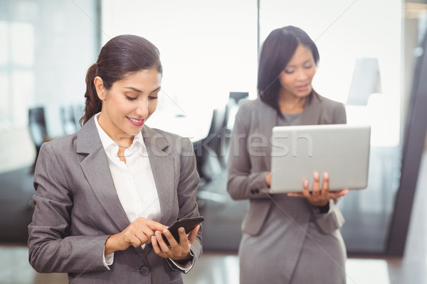 Businesswoman text messaging on mobile phone Stock photo © wavebreak_media