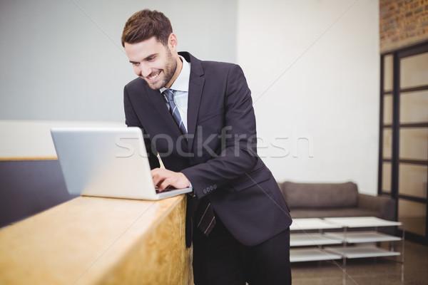Biznesmen za pomocą laptopa Licznik szczęśliwy biuro Zdjęcia stock © wavebreak_media