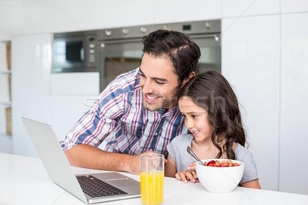 Gülen baba kız dizüstü bilgisayar kullanıyorsanız kahvaltı tablo Stok fotoğraf © wavebreak_media