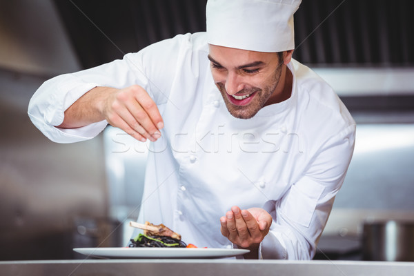 Stock photo: Chef sprinkling spices on dish