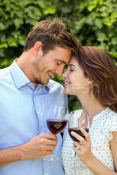 Couple holding wineglasses with eyes closed at front yard Stock photo © wavebreak_media
