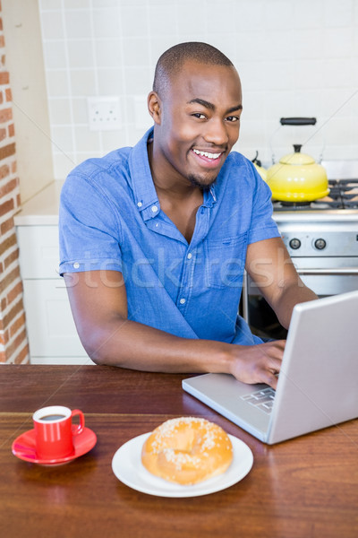 Young man having breakfast and using laptop Stock photo © wavebreak_media