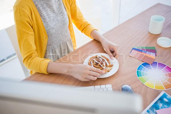 Woman eating breakfast at work Stock photo © wavebreak_media