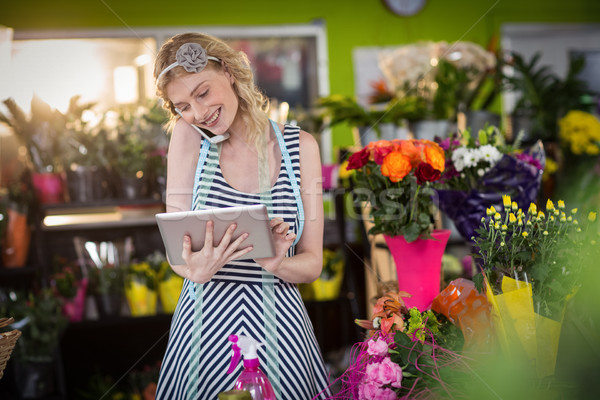 Female florist talking on mobile phone and using digital tablet Stock photo © wavebreak_media