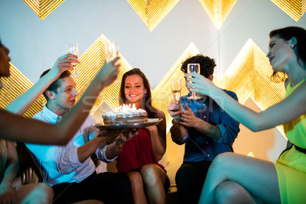Group of smiling friends toasting a glass of champagne while cel Stock photo © wavebreak_media