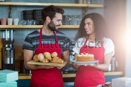 Portrait of waiter and waitress holding a tray of croissants and cake Stock photo © wavebreak_media