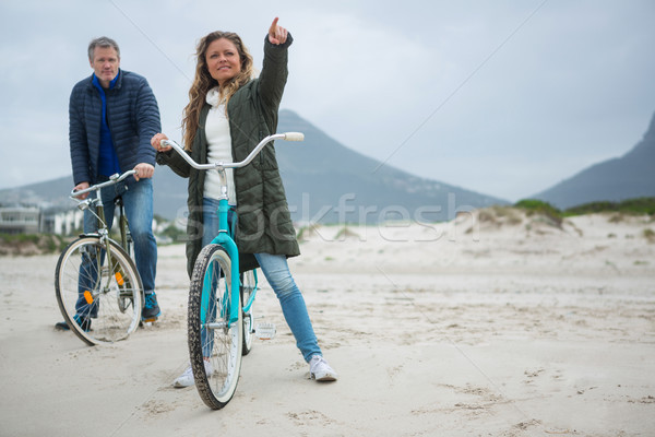Couple on bicycle pointing at distance on beach Stock photo © wavebreak_media