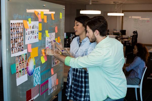 Creativa gente de negocios mirando notas adhesivas vidrio bordo Foto stock © wavebreak_media