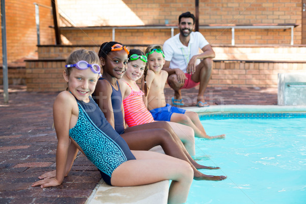 Happy male instructor and children relaxing at poolside Stock photo © wavebreak_media