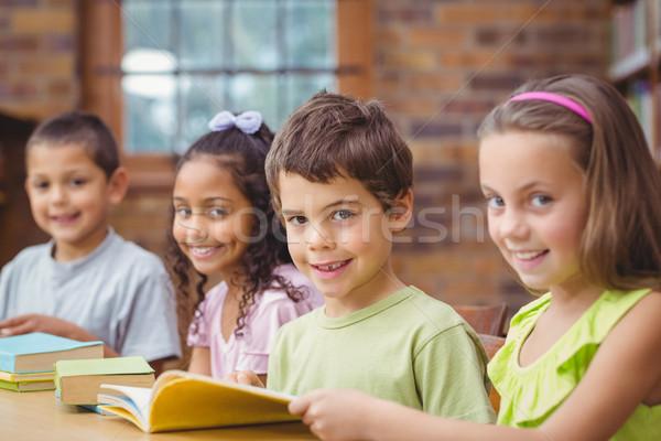 Iskolás olvas könyvek könyvtár boldog gyermek Stock fotó © wavebreak_media