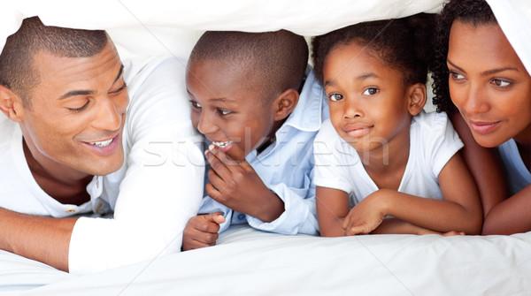 Cheerful family having fun lying down on bed Stock photo © wavebreak_media