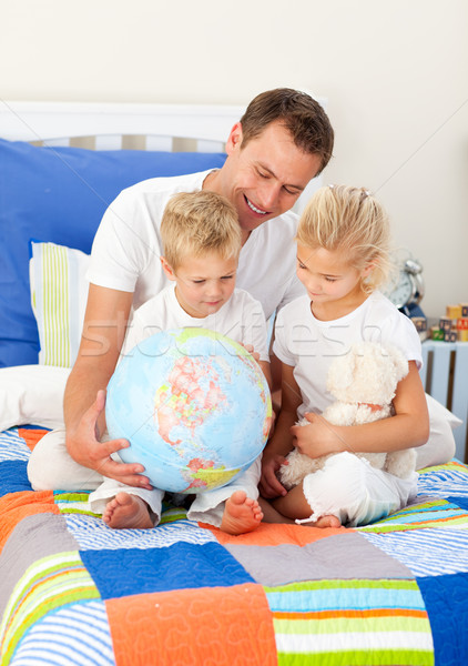 Blond siblings and their father looking at a terrestrial globe Stock photo © wavebreak_media