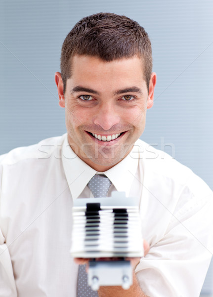Attractive businessman consulting a business-card holder Stock photo © wavebreak_media
