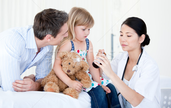 Confident asian female doctor giving syrup to a little girl  Stock photo © wavebreak_media