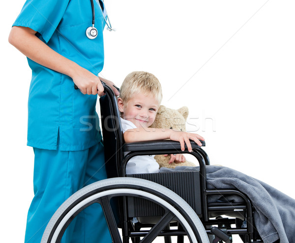 Stock photo: Bright female doctor carrying adorable little boy with his teddy