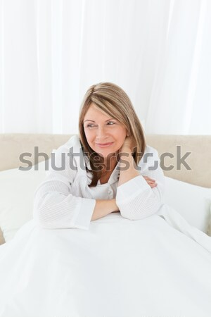 Cute little girl want to sleep siting on her bed Stock photo © wavebreak_media