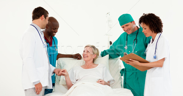 Team of doctors looking after a sick senior patient  against white background Stock photo © wavebreak_media