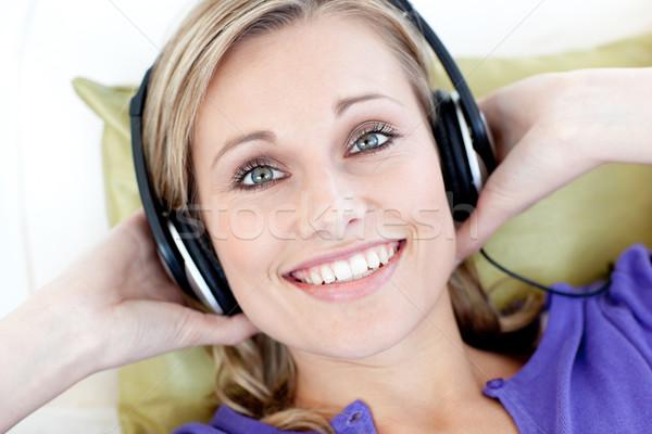 Portret uśmiechnięta kobieta słuchania muzyki patrząc kamery Zdjęcia stock © wavebreak_media