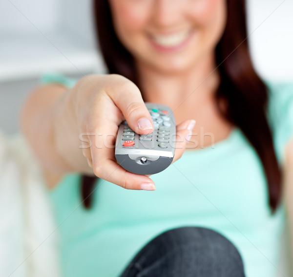 Uśmiechnięta kobieta zdalnego bawialnia domu telewizji Zdjęcia stock © wavebreak_media