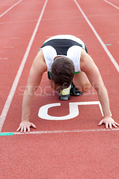 Stock photo: Athletic man waiting in starting block in a stadium