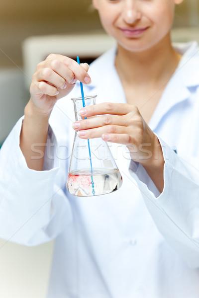 Portrait of a female scientist shaking liquid in an erlenmeyer in her laboratory Stock photo © wavebreak_media