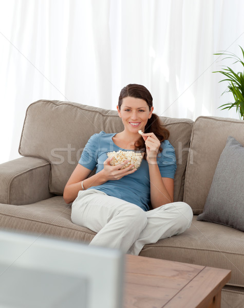 Happy woman eating pop corn while watching television on the sofa at home Stock photo © wavebreak_media