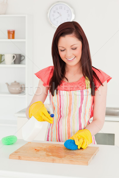 Good looking red-haired woman cleaning a cutting board in the kitchen in her appartment Stock photo © wavebreak_media