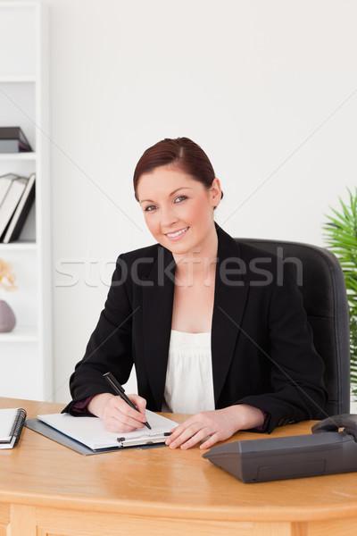 Belo mulher terno escrita bloco de notas posando Foto stock © wavebreak_media