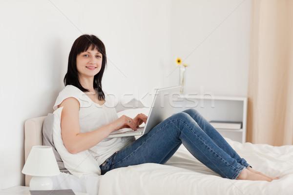 Hermosa morena mujer relajante portátil sesión Foto stock © wavebreak_media