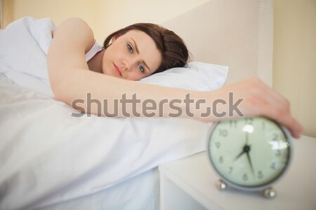 Close up of a cute brunette turning off her alarm clock in her bedroom Stock photo © wavebreak_media