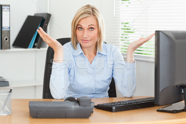 Young blonde woman sitting behind desk not having a clue what to do next in an office Stock photo © wavebreak_media