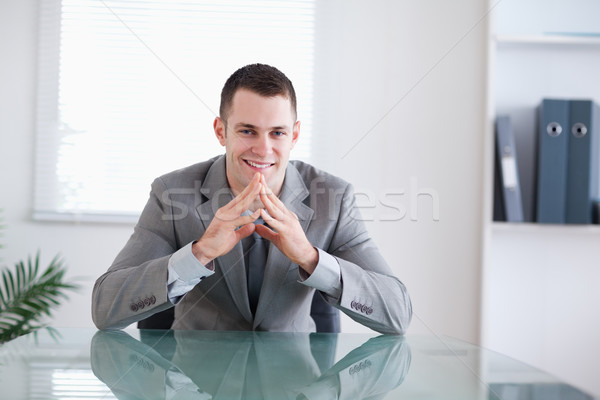 Young businessman smiling sitting behind a table Stock photo © wavebreak_media
