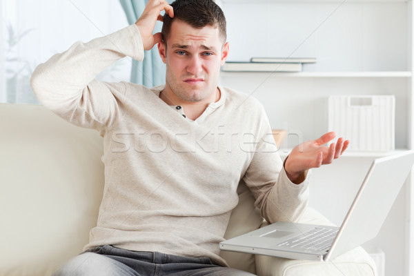 Confused young man using a laptop in his living room Stock photo © wavebreak_media