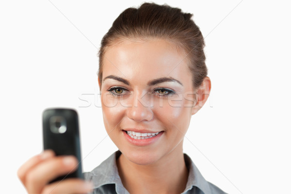Close up of smiling businesswoman reading a text message against a white background Stock photo © wavebreak_media