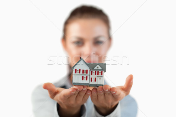 Miniature house being shown by female estate agent against a white background Stock photo © wavebreak_media